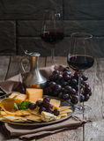 Refined still life of red wine, grapes and cheese. On metal tray on wooden table, dark background Stock Image