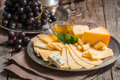 Refined still life of red wine, grapes and cheese. On metal tray on wooden table, dark background Royalty Free Stock Photography