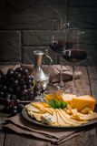Refined still life of red wine, grapes and cheese. On metal tray on wooden table, dark background Royalty Free Stock Photo