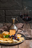 Refined still life of red wine, grapes and cheese. On metal tray on wooden table, dark background Stock Images