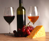 Refined still life of wine, cheese and grapes on wicker tray on wooden table Stock Photo