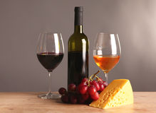 Refined still life of wine, cheese and grapes on wicker tray on wooden table Royalty Free Stock Photos