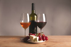 Refined still life of wine, cheese and grapes on wicker tray on wooden table Royalty Free Stock Photo