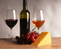 Refined still life of wine, cheese and grapes on wicker tray on wooden table Stock Photography