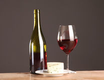 Refined still life of wine, cheese and grapes on wicker tray on wooden table Royalty Free Stock Images