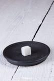 Refined sugar on a black saucer Stock Photos