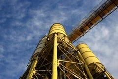 Refinería concreta amarilla con el cielo azul y las nubes Foto de archivo libre de regalías