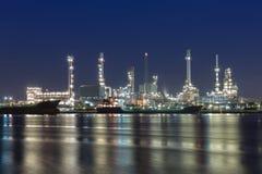 Refinería de petróleo en el crepúsculo con la reflexión del río Foto de archivo libre de regalías