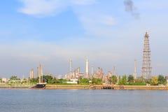 Refinería de petróleo en el río en tiempo de la puesta del sol Imágenes de archivo libres de regalías
