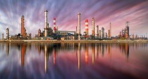Refinería de petróleo en la puesta del sol con la reflexión Fotografía de archivo libre de regalías