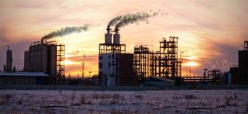 Refinería de petróleo en la puesta del sol. Contaminación del ambiente. Fotografía de archivo libre de regalías