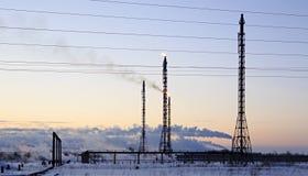 Refinería en el fondo del cielo de la puesta del sol Tarde nevosa escarchada del invierno Foto de archivo libre de regalías