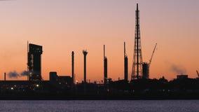 Refinería o fábrica de petróleo en la puesta del sol almacen de video