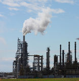 Refinery. Oil refinery billowing smoke into blue sky stock image