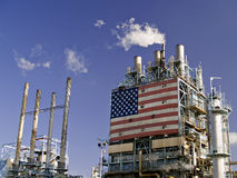 Refinery Complex. Part of an oil refinery complex with a big American flag at the front. Fumes coming out from the chimney (low angle view Royalty Free Stock Image