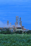 Refinery factory with green field on twilight Stock Photography