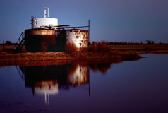 Refinery at night. A refinery reflected in water at night Royalty Free Stock Photos