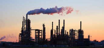 Refinery at Sunset. Oil refinery at sunset with smoke billowing stock photography