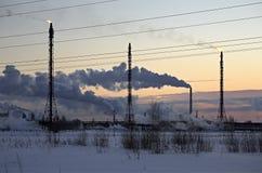 Refinery at sunset sky background. Frosty snowy winter evening Stock Photography