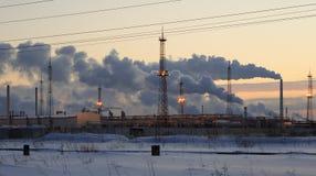 Refinery at sunset sky background. Frosty snowy winter evening. Stock Image