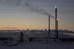 Refinery at sunset sky background. Frosty snowy winter evening. Stock Photography
