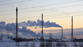 Refinery at sunset sky background. Frosty snowy winter evening. Royalty Free Stock Images