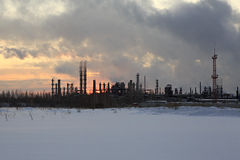 Refinery at sunset sky background. Frosty snowy winter evening. Royalty Free Stock Photo