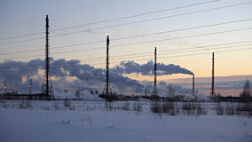 Refinery at sunset sky background. Frosty snowy winter evening. Stock Photo