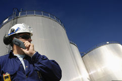 Refinery tanks and engineer. Engineer talking in mobile phone in front of refinery oil tanks, trademarks removed and release enclosed Stock Photo
