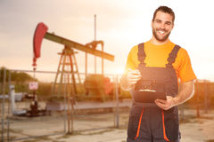 Refinery worker reads the data from the black plates Royalty Free Stock Photos