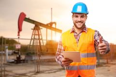 Refinery worker standing in front of the oil pump stock image