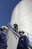 Refinery workers and fuel storage Stock Image