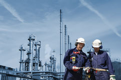 Refinery workers and industry. Two oil workers, engineers with oil and gas refinery, background in blue toning idea Stock Photos