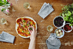 Refining organic healthy pizza with oregano herbs. Baking fresh homemade pizza inviting friends to dinner royalty free stock photo
