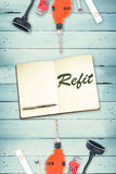 Refit against tools and notepad on wooden background Royalty Free Stock Photography