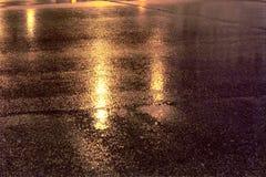 Refléter des lumières sur l'asphalte de route de pluie de nuit image libre de droits