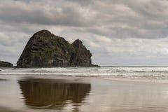 Refléter la roche de lapin à la plage de Piha Photographie stock libre de droits
