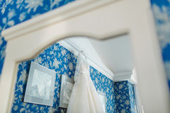 Reflétez la réflexion du ` s de la robe nuptiale crème qui accroche sur la corniche sur un fond le mur floral bleu de modèle Photo stock