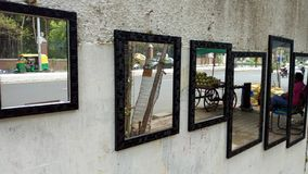 Reflaction of images on the mirror hanging on a road side wall, Vadodara, India stock photos