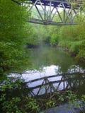Reflecion of an iron arch bridge in a river. A reflecion of an iron arch bridge in a river Royalty Free Stock Photos