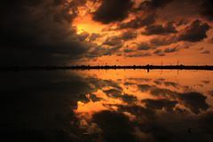 Dramatic clouds sky reflection sunset. Reflecrion sky on water dramatical color yellow golden hours landscape cloudy black stock images