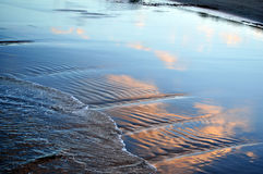 Reflected Clouds. Reflection of clouds in wet sand on the beach. Sunset Stock Photo