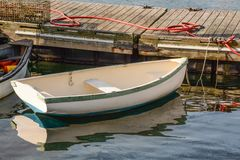 Reflected Dingy. A small dingy tied to the dock in Rockport, Maine Stock Photos