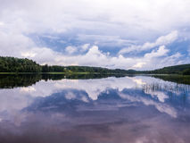 Reflected forest and clouds in lake Royalty Free Stock Images