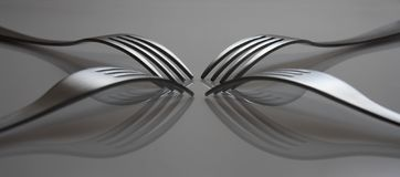 Reflected forks. On a grey background stock image