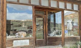 Reflected ghost town in storefront window Royalty Free Stock Image