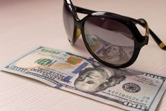 $ 100 is reflected in the glasses . On a beige background royalty free stock photography