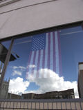 Reflected glory. Flag in a business window with sky and clouds reflected in the glass royalty free stock photography