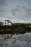 Reflected house. Reflection of a house in the bay, Islay - Scotland Stock Images
