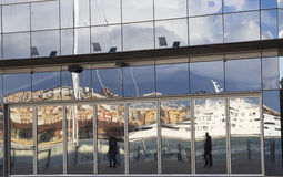 Reflected people in a building glass. Walking in the harbor Stock Photography